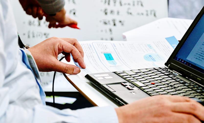 資料を見ながらパソコンを操作する男性