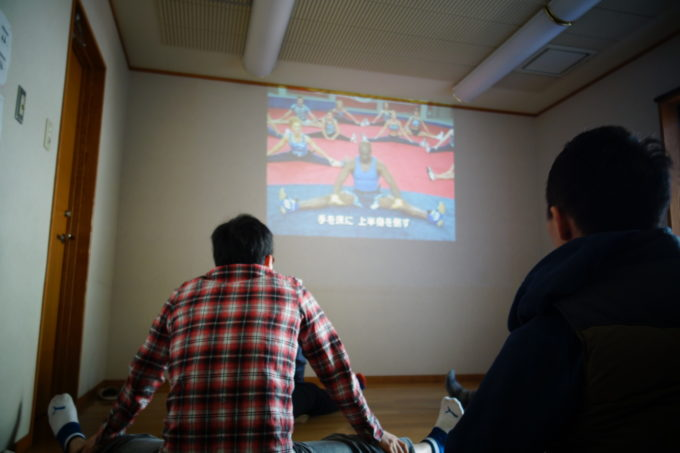 壁に投影された映像を見る研修生