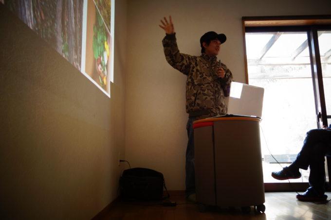プロジェクターを指しながら話をする講師の男性