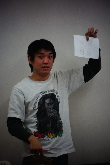 紙を手に持ちかかげる講師