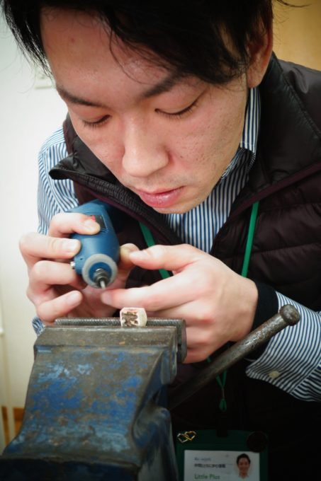 電動工具を使い丁寧に削るスタッフ
