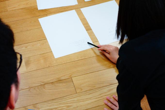 意見が書かれた紙をペンで指しながら議論する研修生