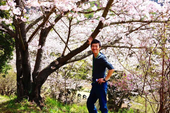 自身が植えた桜の木の下でポーズをとる代表