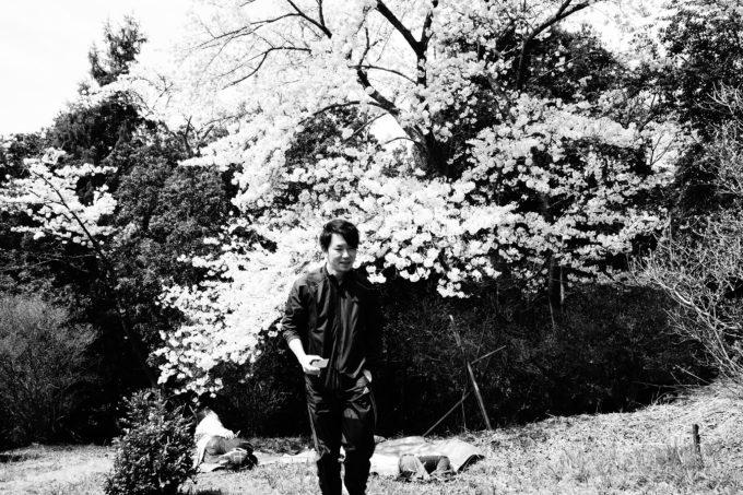 桜の前で写真に写るスタッフの男性