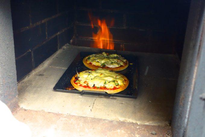 窯の中で焼いている手作りピザ