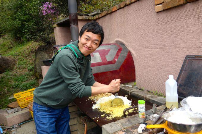 鉄板の上でコテを使いそばめしを焼くく施設長
