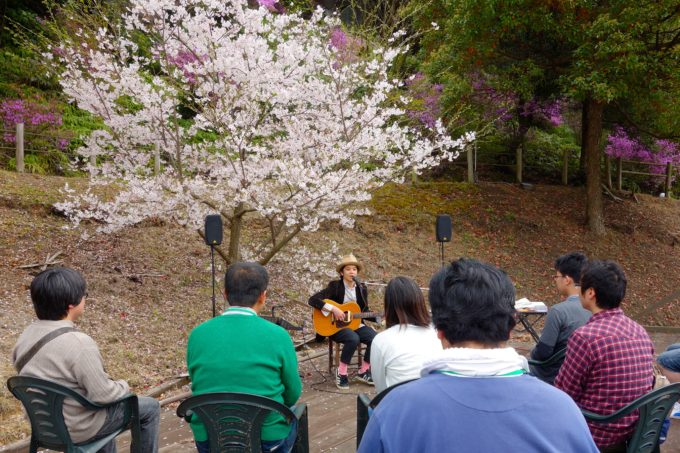 ウッドデッキの上でシンガーソングライターの演奏を聴く参加者