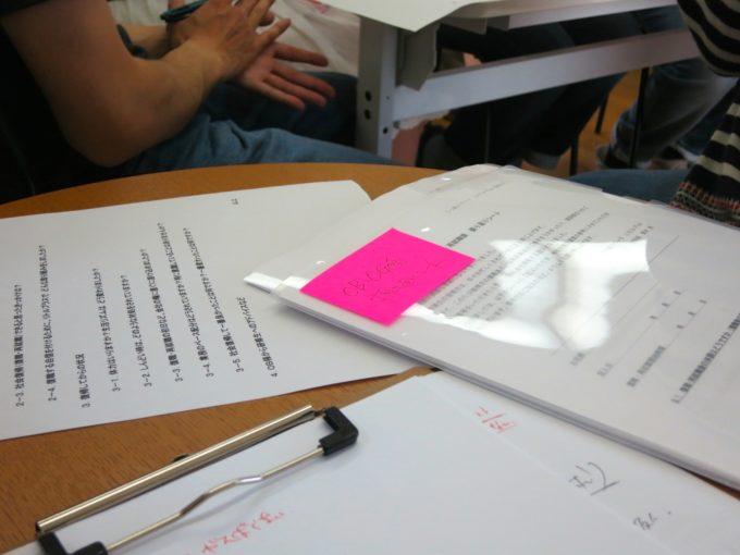テーブルの上に置かれたビンク色のメモ付箋が貼られた資料