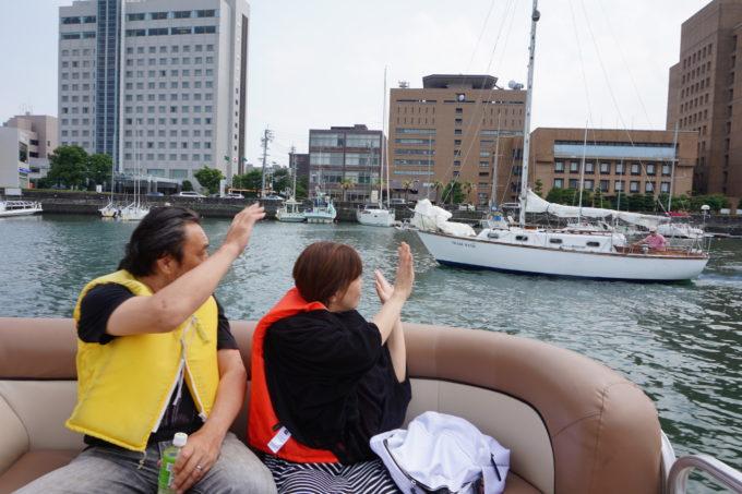 他の船に手を振る男性と女性