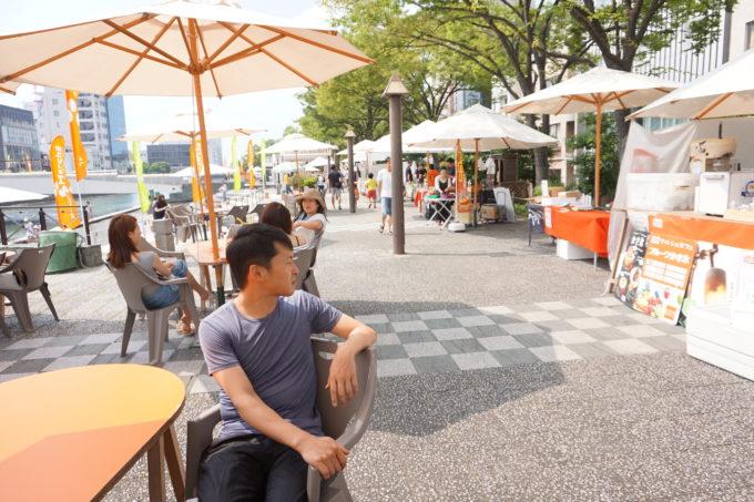 徳島のマルシェ会場でパラソルの下に座る男性