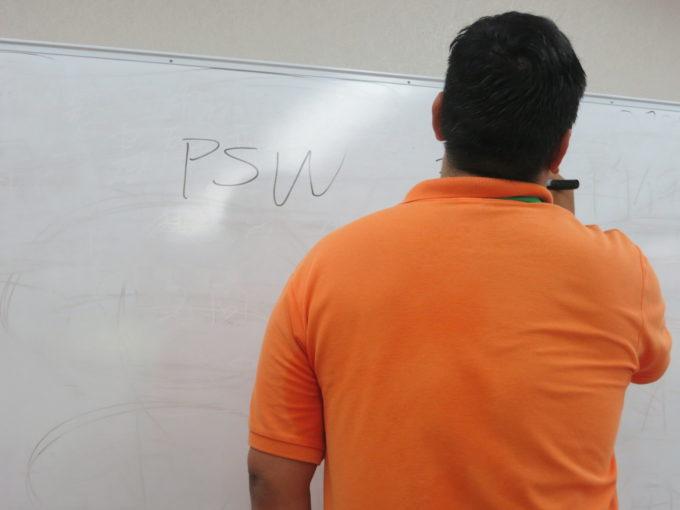 ホワイトボードに書き込むオレンジ色の服の男性