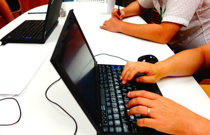 机に並んでパソコンを操作する研修生
