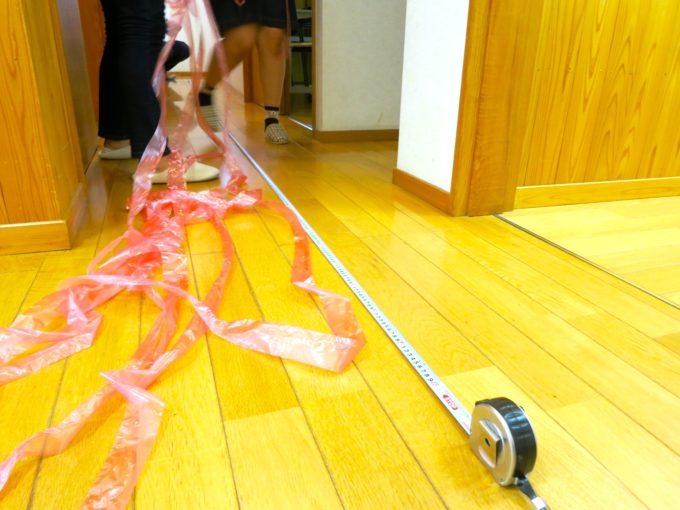 廊下でスケールを使い長さを図る様子