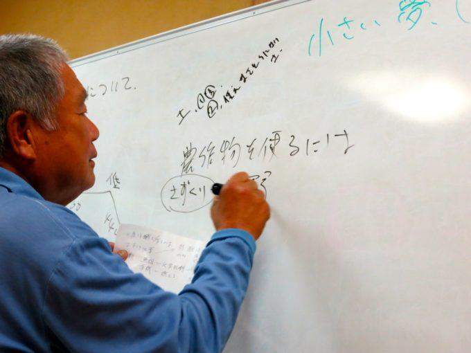 ホワイトボードに書きこみながら講義をする農園の社長