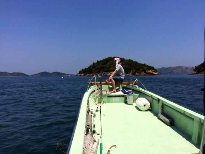 船の先頭に座って海を眺める施設長