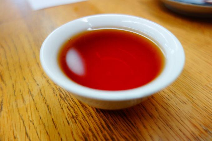 白い茶器に淹れられた紅色のお茶