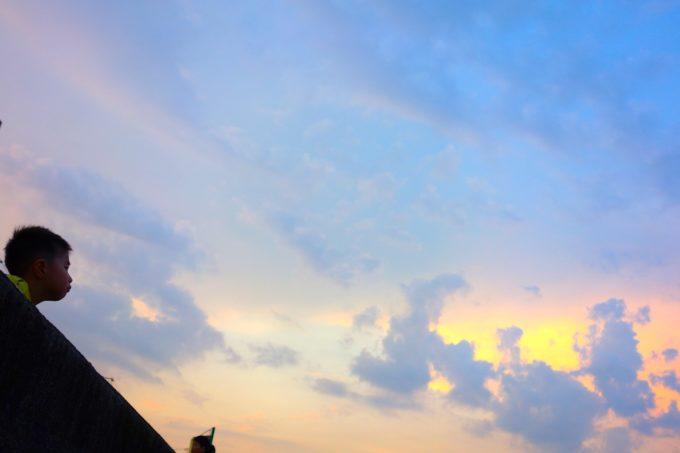 夕焼け空の下花火を待つ少年