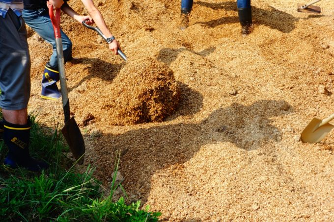 スコップを使い手作業で耕す研修生たち