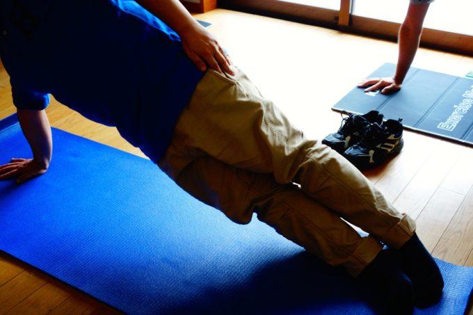 マットを敷いて運動をする研修生