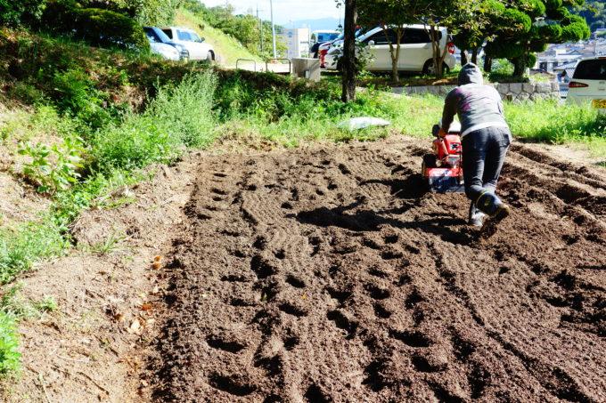 農機具を使い畑を耕す男性