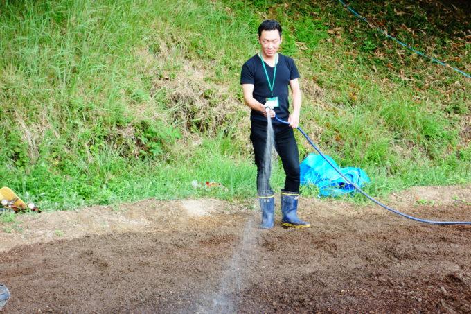 ホースで水を撒く男性スタッフ