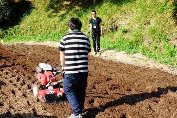 農園を農機具を使って耕す男性と水をやる男性