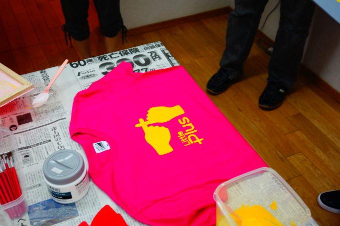 黄色でリトルプラスと書かれたピンク色のTシャツ