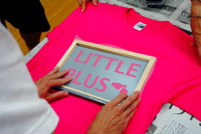 Tシャツの上でインクを塗る位置を決める研修生