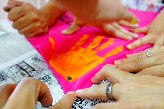 ピンクの布に手形をする多くの手