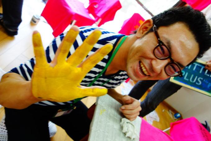 手のひらが黄色のインクに染まった男性スタッフ