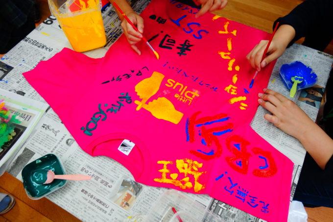 様々な色のインクで寿司など書かれたかれたピンクのTシャツ