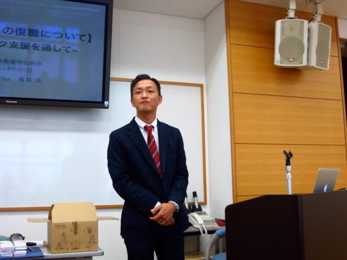 スーツ姿でプロジェクトの前にたつ施設長