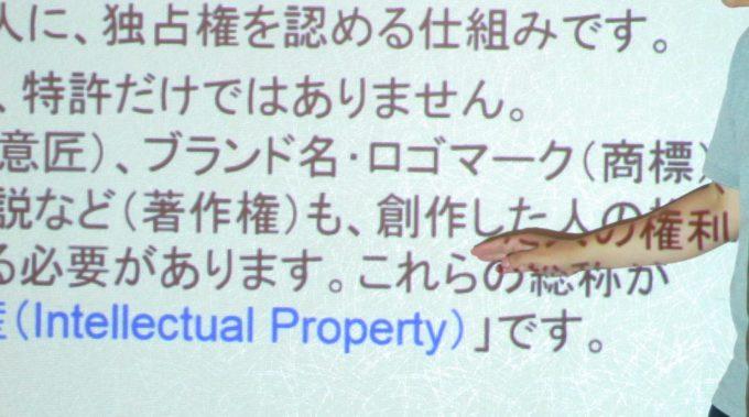 プロジェクターに投影された画面を説明する人の手