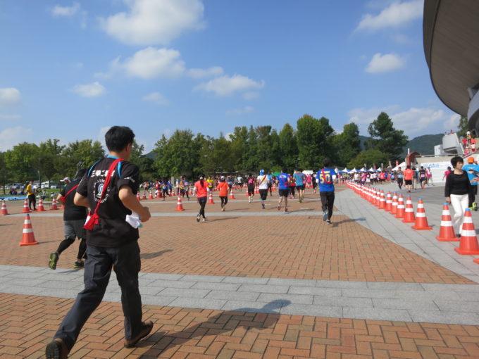 スタジアムの周りを走るランナーの後ろ姿