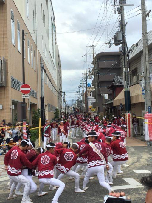 赤い揃いの法被を着た祭り参加者