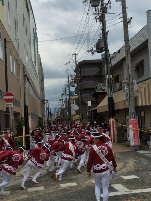 一気に綱を引く赤い法被の祭り参加者