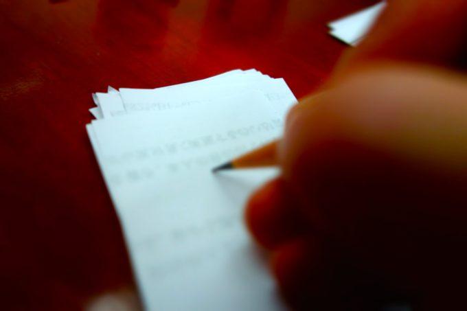 小さい紙に何かを書きこむ様子