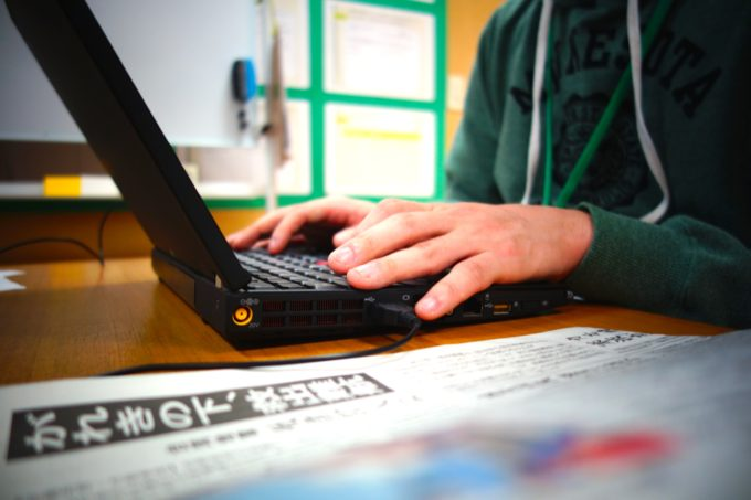 新聞を見ながらパソコンを操作する研修生