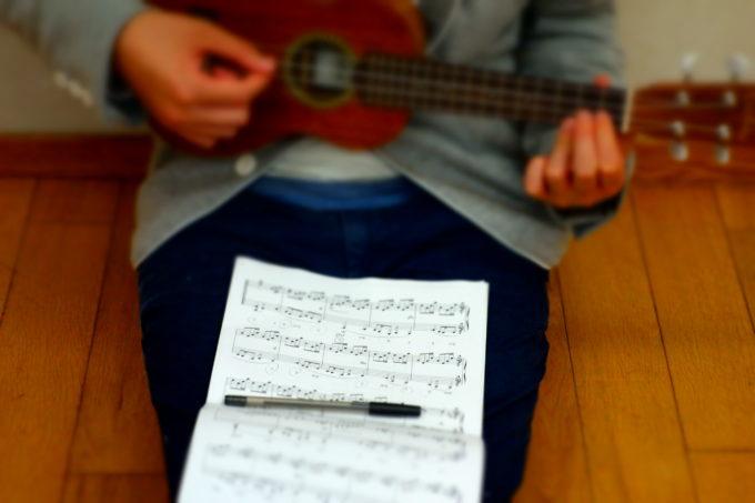楽譜を見ながらウクレレを練習する様子