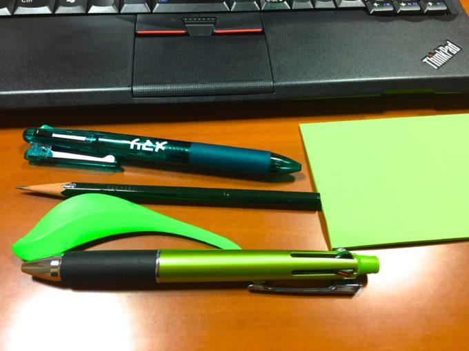 テーブルに置かれたパソコンやボールペンなど