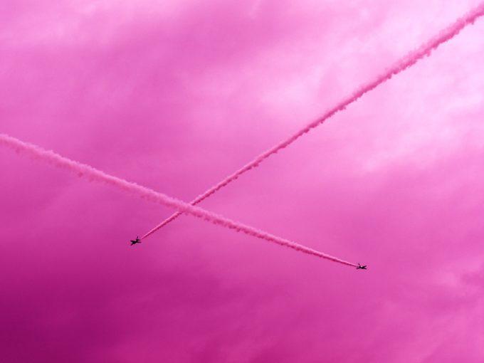 ピンク色のスモークを出しながら空を飛ぶ飛行機