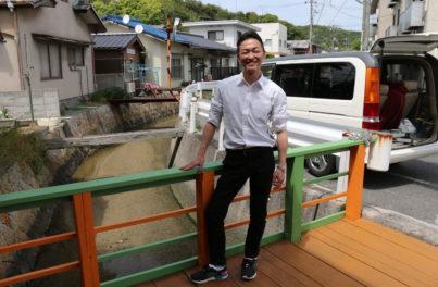 塗装作業が完成した橋の上で、よろこびの表情を浮かべる施設長